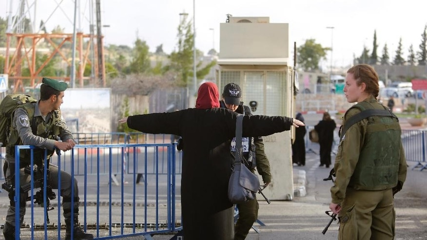 Israeli security forces search a Palestinian woman at a checkpoint as she makes her way to attend the first Friday prayers in Jerusalem's al-Aqsa mosque during Muslim holy month of Ramadan, in the West bank city of Bethlehem, Friday, June 10, 2016. (AP Photo/Nasser Shiyoukhi)