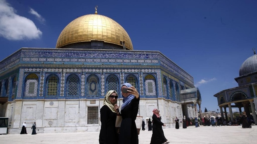 Palestinian women take a picture during the Muslim holy month of Ramadan at the Dome of the Rock Mosque in the Al Aqsa Mosque compound in Jerusalem's Old City, Friday, June 10, 2016. (AP Photo/Mahmoud Illean)