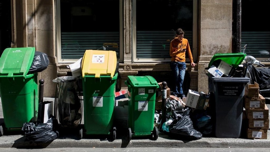 A man rests past overflowing garbage cans and rubbish bags in Paris, France, Thursday, June 9, 2016. After a rough couple of months which have included protests, fuel shortages, rail strikes and once-in-a-generation floods, France's capital is facing a new challenge : Piles of uncollected trash. (AP Photo/Kamil Zihnioglu)