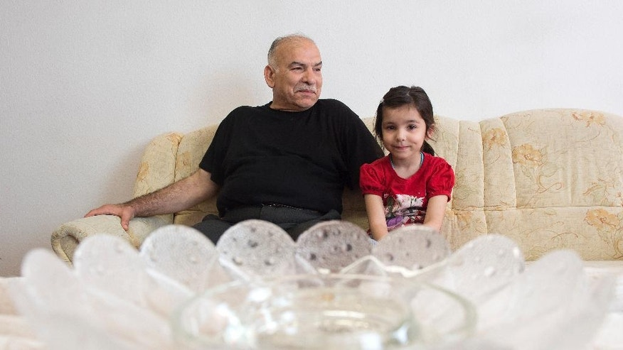 In this May 30, 2016 picture Abed Alsalam Lahafi,  from Aleppo sits besides his 7-year-old daughter Sima in their home for asylum seekers in Hettstedt, Germany. Where once 20,000 people lived in Hettstedt  there are now 15,000; another 5,000 are forecast to vanish in the coming decade. The man who hopes to avert this demographic disaster is a jovial 38-year-old lawyer with a radical idea. Why not take advantage of the influx of migrants to Germany and settle refugees in the town, argues Danny Kavalier, Hettstedt's mayor since 2011.  (AP Photo/Jens Meyer)