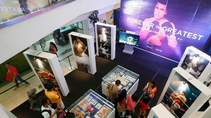 "Filipino fans look at memorabilia from the ""Thrilla in Manila"" World Heavyweight boxing fight between Muhammad Ali and Joe Frazier at the launch of an exhibit at The Ali Mall in suburban Quezon city northeast of Manila, Philippines to pay tribute to Muhammad Ali who died exactly a week ago Friday, June 10, 2016. The fight was dubbed the ""Most Legendary Fight in History"". (AP Photo/Bullit Marquez)"