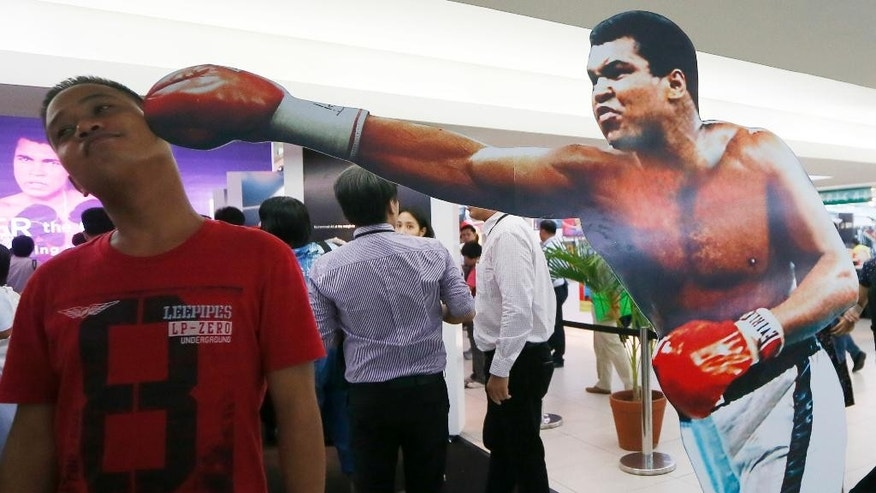 "A Filipino fan poses before a standee of Muhammad Ali during the launch of an exhibit of photos and memorabilia of the ""Thrilla in Manila"" World Heavyweight boxing fight between Muhammad Ali and Joe Frazier at The Ali Mall in suburban Quezon city northeast of Manila, Philippines Friday, June 10, 2016. The exhibit was launched to pay tribute to Muhammad Ali who died exactly a week ago Friday. (AP Photo/Bullit Marquez)"