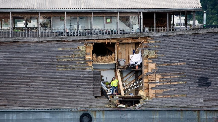 A crew member inspects the damage of the hull of a wooden exhibition ship built as a representation of Noah's Ark after it crashed into a moored Coast Guard vessel in Oslo harbour, Friday June 10, 2016. (Hkon Mosvold Larsen, NTB Scanpix) NORWAY OUT