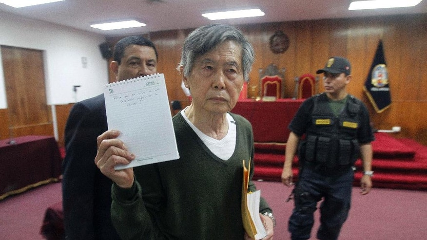 "FILE - In this Nov. 28, 2013 file photo, Peru's jailed former President Alberto Fujimori holds up a notepad with a message that reads in Spanish ""Why do you summon an accused man who is sick with cancer?"" as he leaves his court hearing at a police base on the outskirts of Lima, Peru. Peru's apparent president-elect says he is open to the possibility of granting house arrest to Fujimori. Pedro Pablo Kuczysnki reiterated the campaign pledge in his first interview since declaring himself the victor in the June 5, 2016 election over the imprisoned ex-president's daughter, Keiko Fujimori. Alberto Fujimori is serving 25 years for corruption and supporting death squads during his authoritarian rule in the 1990s. (AP Photo/Karel Navarro, File)"