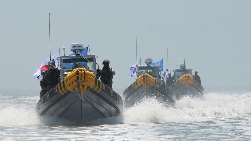 In this photo provided by the South Korean Defense Ministry, South Korean marines and navy soldiers on boats conduct a crackdown against China's illegal fishing in neutral waters around Ganghwa island, South Korea, Friday, June 10, 2016. South Korean military vessels started an operation Friday to repel Chinese fishing boats illegally harvesting prized blue crabs from an area near Seoul's disputed sea boundary with North Korea. (The South Korean Defense Ministry via AP)