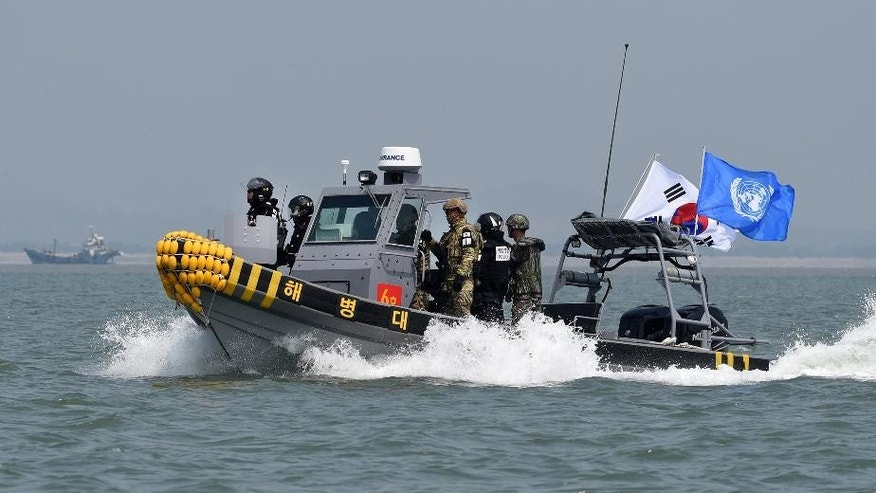 In this photo provided by the South Korean Defense Ministry, South Korean marines and navy soldiers on a boat conduct a crackdown against China's illegal fishing in neutral waters around Ganghwa island, South Korea, Friday, June 10, 2016. South Korean military vessels started an operation Friday to repel Chinese fishing boats illegally harvesting prized blue crabs from an area near Seoul's disputed sea boundary with North Korea. (The South Korean Defense Ministry via AP)