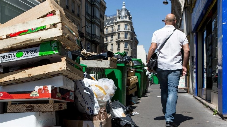 A man walks past a overflowing pile of rubbish bags in Paris, France, Thursday, June 9, 2016. After a rough couple of months which have included protests, fuel shortages, rail strikes and once-in-a-generation floods, France's capital is facing a new challenge : Piles of uncollected trash. (AP Photo/Kamil Zihnioglu)