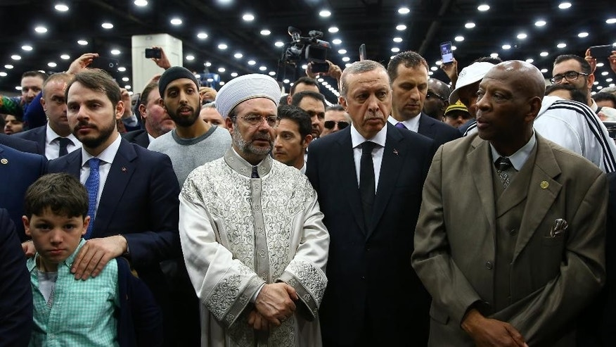 Turkey's President Recep Tayyip Erdogan, second right, Mehmet Gormez, the head of Turkey's Religious Affairs, second left, and Berat Albayrak, Turkish Energy Minister and son-in-law of Erdogan, left, attend Muhammad Ali's Jenazah, a traditional Muslim service, in Freedom Hall in Louisville, Ky, USA, Thursday, June 9, 2016.  Officials say Turkey's president, who flew to the United States to attend the funeral of Muhammad Ali, is cutting short his visit and returning home, according to Private Dogan news agency, which reported that the Turkish leader was upset that funeral organizers rejected his request to lay a piece from the cloth covering the Kaaba, in Mecca, on Ali's coffin. (Kayhan Ozer, Presidential Press Service/Pool via AP)
