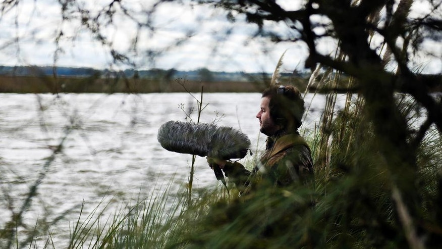 In this June 1, 2016 photo, Juan Pablo Culasso stands in a natural reserve with his recording equipment, on the outskirts of Montevideo, Uruguay. Born blind, Culasso has never seen a bird. But through his gifted sense of hearing, he can tell the difference among more than 720 species and identify more than 3,000 different bird sounds. (AP Photo/Matilde Campodonico)