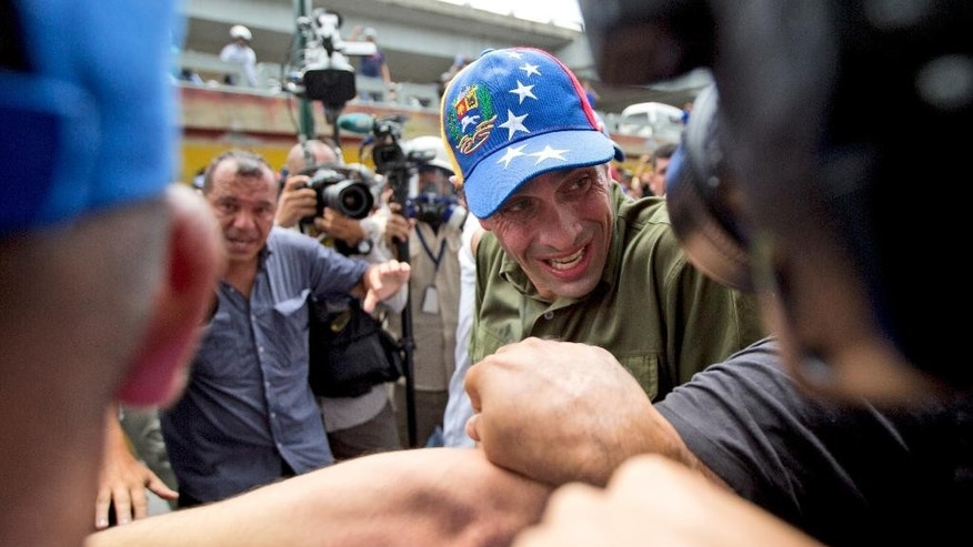 Opposition leader Henrique Capriles reacts after getting pepper sprayed by Bolivarian National Police during a protest in Caracas, Venezuela, Tuesday, June 7, 2016. Protesters were turned back from the headquarters of Venezuela's electoral body where the group attempted to march to demand the government allow it to pursue a recall referendum against President Nicolas Maduro. (AP Photo/Fernando Llano)