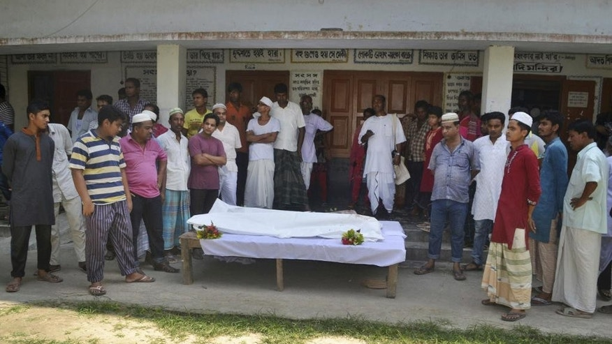 FILE- In this June 10, 2016 file photo, Bangladeshi people surround the body of a Hindu holy man after assailants hacked him to death in Pabna, 275 kilometres (170 miles) from Dhaka, Bangladesh. Authorities have rounded up about 1,600 criminal suspects, including a few dozen believed to be Islamist radicals, in a nationwide crackdown aimed at halting a wave of brutal attacks on minorities and activists in Bangladesh, police said Saturday, June 11, 2016. (AP Photo, File)