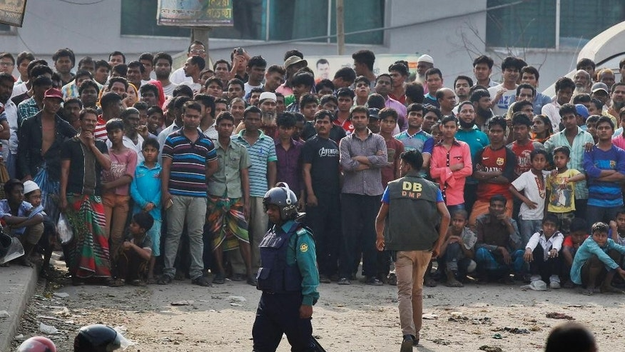 FILE- This Feb. 20, 2016 file photo shows local residents watching a police raid on a building in Dhaka, Bangladesh. Authorities have rounded up about 1,600 criminal suspects, including a few dozen believed to be Islamist radicals, in a nationwide crackdown aimed at halting a wave of brutal attacks on minorities and activists in Bangladesh, police said Saturday, June 11, 2016. (AP Photo, File)