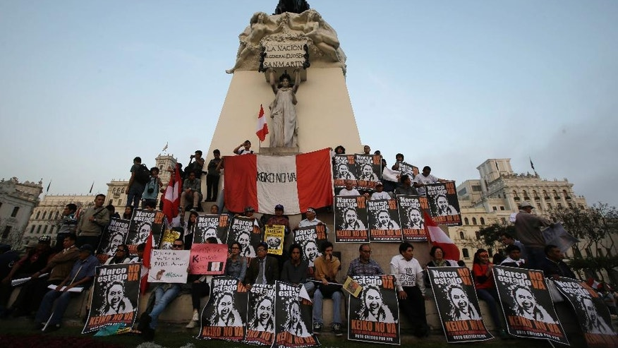 """FILE - In this May 31, 2016 file photo, demonstrators hold posters with a message that reads in Spanish; """"Reject the Narco State, reject Keiko,"""" during a protest against presidential candidate Keiko Fujimori, at Plaza San Martin in downtown Lima, Peru. The campaign has left a bitter residue in part because Kuczynski accused his rival of being the harbinger of a """"narco-state"""". In conceding on Friday, June 10, 2016, Fujimori blasted politicians, business leaders and members of the media for orchestrating a """"hate-filled"""" campaign to discredit her candidacy. (AP Photo/Martin Mejia, File)"""