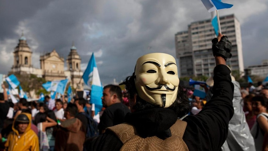 A demonstrator wears a Guy Fawkes mask on the back of his head at a protest against corruption outside the National Palace in Guatemala City, Saturday, June 11, 2016. Protesters gathered at Plaza Central to demand justice in the new cases of corruption against former President Otto Perez Molina and vice-president Roxana Baldetti. Both former leaders are jailed awaiting trial in multiple corruption cases. (AP Photo/Moises Castillo)