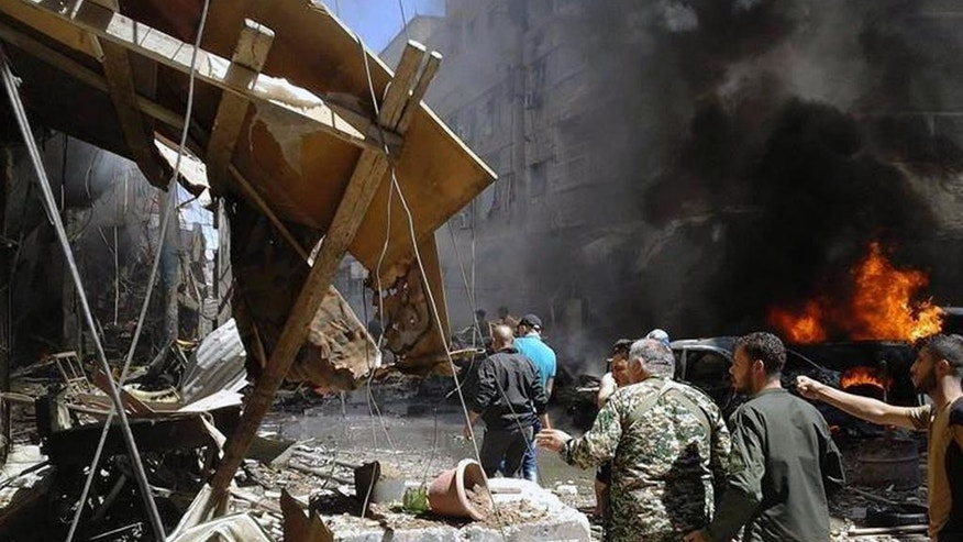 In this photo released by the Syrian official news agency SANA, Syrians gather around damaged buildings after a bomb attack at the Sayyida Zeinab suburb, Damascus, Syria, Saturday, June 11, 2016. Two bombs went off Saturday near the Syrian capital, killing at least eight people and wounding over a dozen others in the latest attack to hit the predominantly Shiite area in recent months, state TV and an opposition activist group said. (SANA via AP)