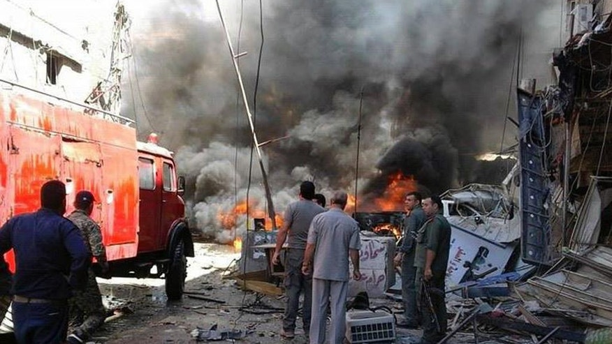 In this photo released by the Syrian official news agency SANA, Syrians gather around burning buildings after a bomb attack at the Sayyida Zeinab suburb, Damascus, Syria, Saturday, June 11, 2016. Two bombs went off Saturday near the Syrian capital, killing at least eight people and wounding over a dozen others in the latest attack to hit the predominantly Shiite area in recent months, state TV and an opposition activist group said. (SANA via AP)