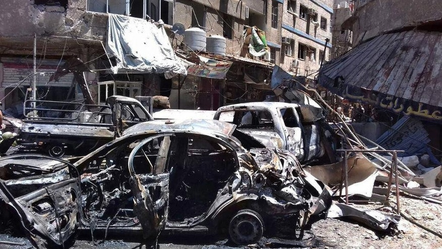 This photo released by the Syrian official news agency SANA, shows the scene after a bombing attack at the Sayyida Zeinab suburb, Damascus, Syria, Saturday, June 11, 2016. Two bombs went off Saturday near the Syrian capital, killing at least eight people and wounding over a dozen others in the latest attack to hit the predominantly Shiite area in recent months, state TV and an opposition activist group said. (SANA via AP)