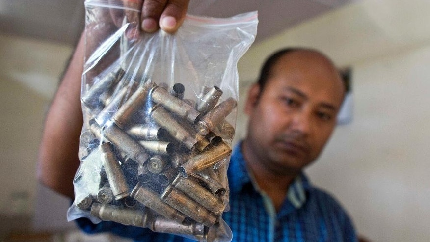 FILE- In this April 14, 2016 file photo, a forest official shows shell casings that were recovered from a site where a rhinoceros was killed by poachers with AK-47 at Kaziranga, India. The newly elected government of the northeast Indian state of Assam is launching new plans to crack down on the poaching of the area's famed one-horned rhinos. The state's Kaziranga National Park is home to the world's largest population of the rare rhinos. While overall poaching deaths have dropped over the last few years, a series of rhino killings this year has led the new government to renew its anti-poaching efforts. (AP Photo/ Anupam Nath, File)