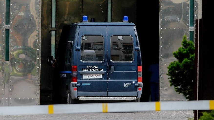 A penitentiary police van is driven through a gate of the Rebibbia prison in Rome, Friday, June 10, 2016. The Eritrean man extradited to Italy under great fanfare as an alleged kingpin of a migrant smuggling ring told authorities on Friday that his arrest in Sudan was a case of mistaken identity, his lawyer, said. ''It is clear for him he is not the man who is smuggling or trafficking humans,'' Michele Calantropo said outside the Rome Rebibiba prison where the suspect was questioned by prosecutors from Sicily leading Italy's anti-smuggling investigations in the presence of a judge. (AP Photo/Fabio Frustaci)