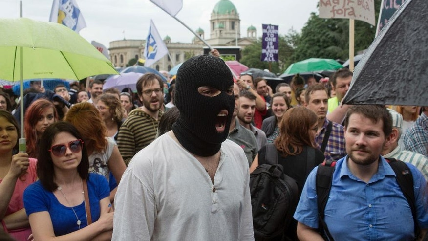 A man wears a balaclava as he and others chant slogans during a protest in Belgrade, Serbia, Saturday, June 11, 2016. Several thousand gathered in central Belgrade to protest the controversial demolition of buildings in a city district designated to be developed by a consortium from the United Arab Emirates. (AP Photo/Marko Drobnjakovic)