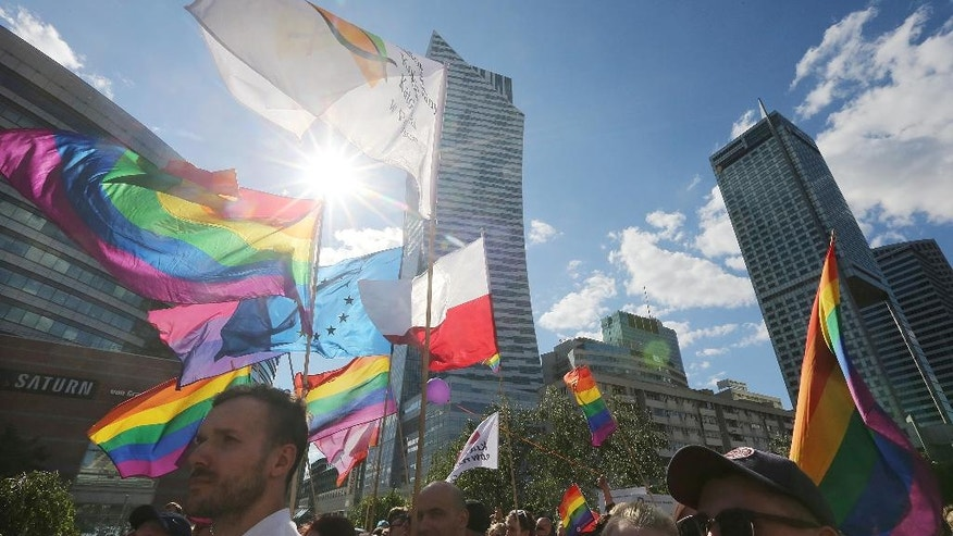 Thousands of Warsaw residents with rainbow flags walk in a colorful annual Equality Parade to show their support for sexual minority groups  in Warsaw, Poland, Saturday, June 11, 2016. The 16th parade Saturday is held at a time when views concerning minorities are getting radicalized under a right-wing government that took office in November. A visible police presence accompanied the march.(AP Photo/Czarek Sokolowski)