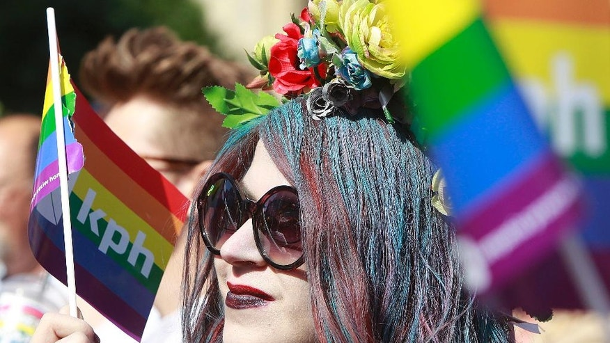 Warsaw resident with rainbow flags walk in a colorful annual Equality Parade to show their support for sexual minority groups  in Warsaw, Poland, Saturday, June 11, 2016. The 16th parade Saturday is held at a time when views concerning minorities are getting radicalized under a right-wing government that took office in November. A visible police presence accompanied the march.(AP Photo/Czarek Sokolowski)