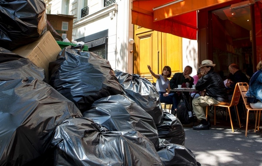People have lunch past overflowing rubbish bags in Paris, France, Thursday, June 9, 2016. After a rough couple of months which have included protests, fuel shortages, rail strikes and once-in-a-generation floods, France's capital is facing a new challenge : Piles of uncollected trash. (AP Photo/Kamil Zihnioglu)