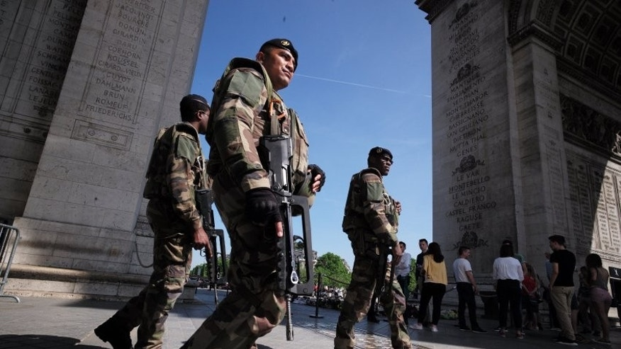 Soldiers near the Eiffel tower in Paris on Thursday, one day before the start of Euro 2016.