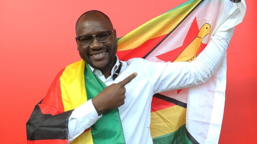 "This photo taken Tuesday May 3, 2016 shows Evans Mawarire, a young pastor, posing with a Zimbabwean flag wrapped around his body, in Harare.  Mawarire launched a media campaign called Thisflag"" to protest alleged government failures and asserting the meaning of the national emblem. (AP Photo/Tsvangirayi Mukwazhi)"