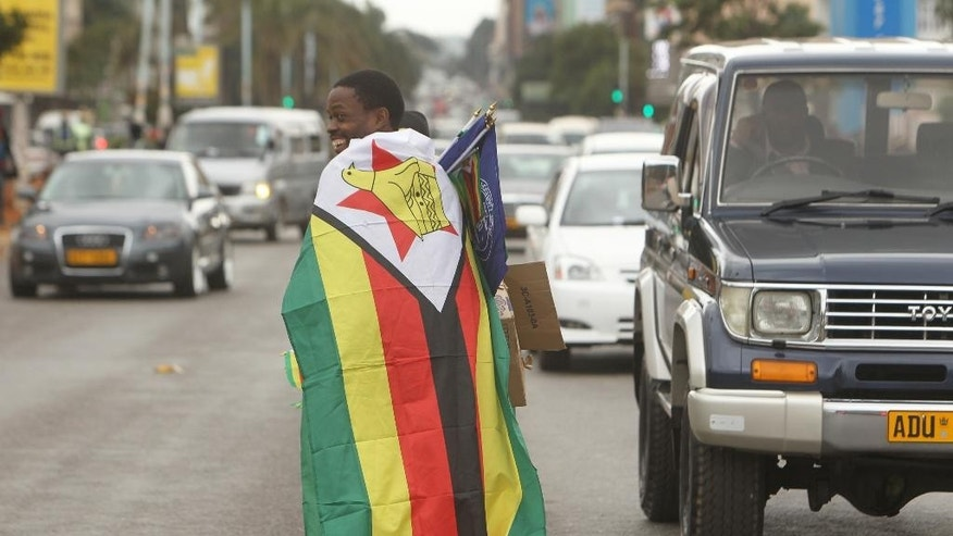 "This photo taken Wednesday May 18, 2016 shows a vendor selling Zimbabwean flags in Harare.  The young pastor, Evans Mawarire has launched a media campaign called Thisflag"" to protest alleged government failures and asserting the meaning of the national emblem. (AP Photo/Tsvangirayi Mukwazhi)"