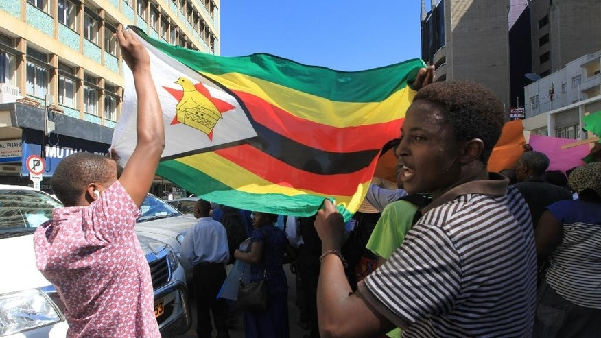 "This photo taken Wednesday May 18, 2016,  Christians march while drandishing the Zimbabwean national flag in Harare. The young pastor, Evans Mawarire has launched a media campaign called Thisflag"" to protest alleged government failures and asserting the meaning of the national emblem. (AP Photo/Tsvangirayi Mukwazhi)"