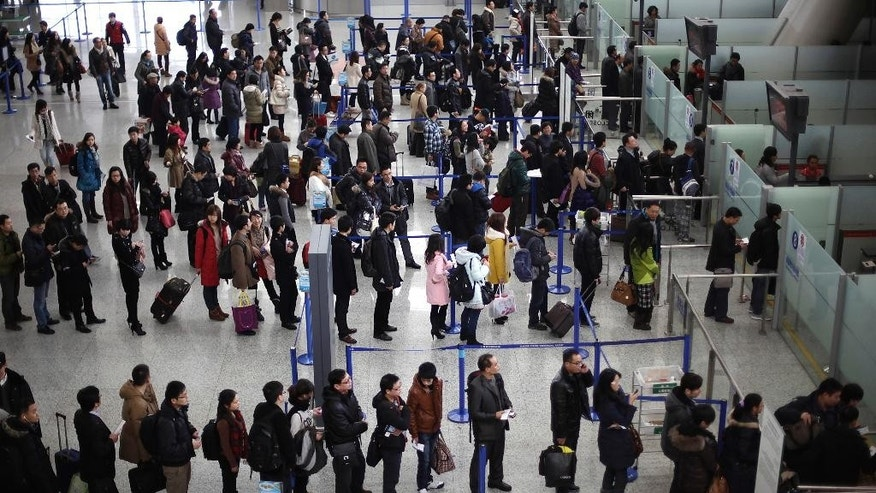 FILE - In this Jan. 20, 2012, file photo, passengers queue up for a security check at Pudong International Airport in Shanghai, China. A small explosion at a check-in area of Shanghai's Pudong airport injured a few people Sunday, June 12, 2016, Chinese authorities said. (AP Photo/Eugene Hoshiko, File)