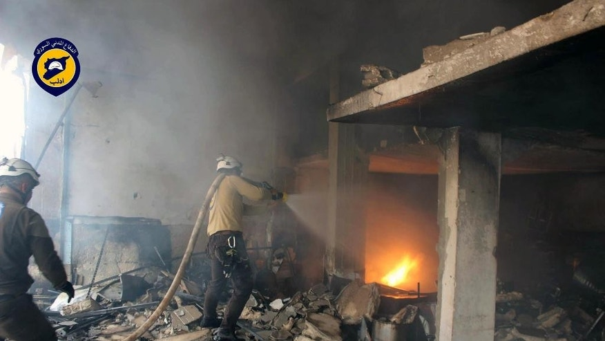This photo provided by the Syrian Civil Defence White Helmets, which has been authenticated based on its contents and other AP reporting, shows Civil Defense workers putting out a fire in a building following airstrikes hit a market area in Idlib, Syria, Sunday, June. 12, 2016. Anti-government activists said that airstrikes have hit a market and other targets in the northwestern Syrian city of Idlib, killing at least 12 people. (Syrian Civil Defence White Helmets via AP)