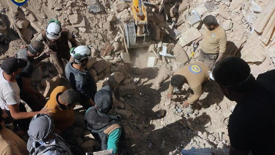 This photo provided by the Syrian Civil Defence White Helmets, which has been authenticated based on its contents and other AP reporting, shows Civil Defense workers and Syrian citizens inspect damage buildings after airstrikes hit a market area in Idlib, Syria, Sunday, June. 12, 2016. Anti-government activists said that airstrikes have hit a market and other targets in the northwestern Syrian city of Idlib, killing at least 12 people. (Syrian Civil Defence White Helmets via AP)