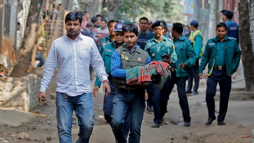 FILE- In this Dec. 24, 2015 file photo,a member of Bangladeshi bomb disposal unit carries seized homemade bombs during a raid on a building where members of a banned Islamist group were detained in Mirpur area, Dhaka, Bangladesh. Authorities in Bangladesh said Sunday, June 12, 2016 that they have arrested more than 5,000 criminal suspects in the past few days as they continue a nationwide crackdown to try and stop a growing wave of brutal attacks on minorities and activists in the country. (AP Photo, File)