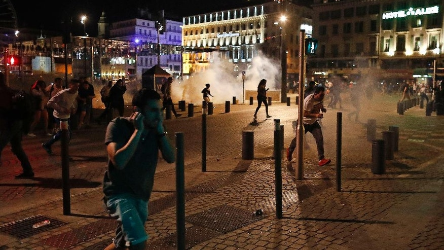People run after police fired tear gas following clashes after the Euro 2016 soccer championship group B match between England and Russia in Marseille, France Saturday, June 11, 2016. Clashes between soccer fans Saturday in Marseille's Old Port occurred for a third straight day of violence in the city. (AP Photo/Darko Bandic)