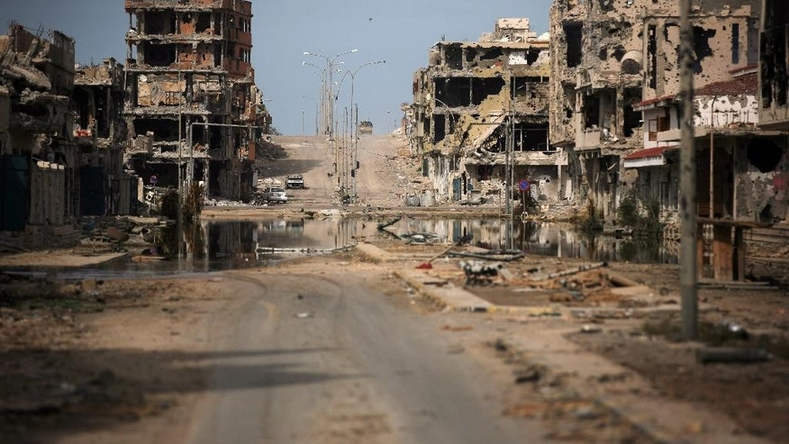 FILE - This Oct. 22, 2011 file photo, shows a general view of buildings ravaged by fighting in Sirte, Libya. A spokesman for militias loyal to Libya's U.N.-brokered government said on Sunday, June 12, 2016 that Islamic State militants have barricaded themselves in the center of their stronghold in the coastal city of Sirte, hoping to draw their attackers into a protracted street battle. Brig-Gen. Mohammed al-Ghasri said the militants have barricaded themselves in a densely built-up area and their snipers taken positions on rooftops waiting for the militias to advance. (AP Photo/Manu Brabo, File)