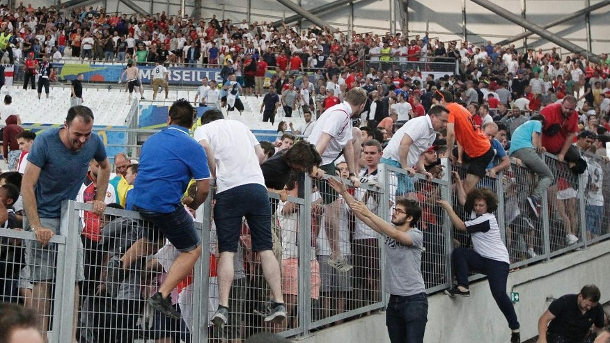 Spectators run on the stands as clashes break out right after the Euro 2016 Group B soccer match between England and Russia, at the Velodrome stadium in Marseille, France, Saturday, June 11, 2016. (AP Photo/Thanassis Stavrakis)