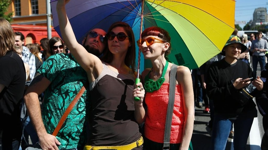 Ukrainian gay rights activists pose for a selfie as they take part in a event in Kiev, Ukraine, Sunday, June 12, 2016.  Authorities sanctioned gay rights marches after the new pro-Western government came into office, and police forces were guarding the procession in central Kiev, Sunday, to protect against far-right groups.(AP Photo/Sergei Chuzavkov)
