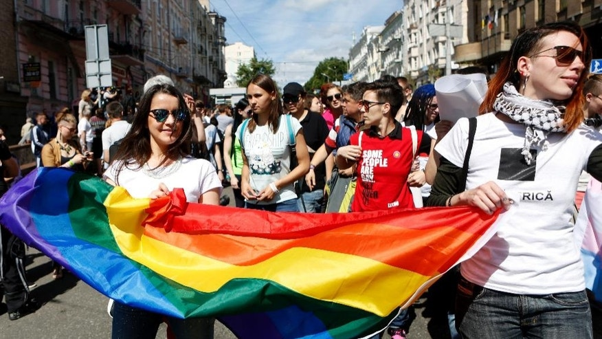 Ukrainian gay rights activists take part in a march in Kiev, Ukraine, Sunday, June 12, 2016.  Authorities sanctioned gay rights marches after the new pro-Western government came into office, and police forces were guarding the procession in central Kiev, Sunday, to protect against far-right groups.(AP Photo/Sergei Chuzavkov)
