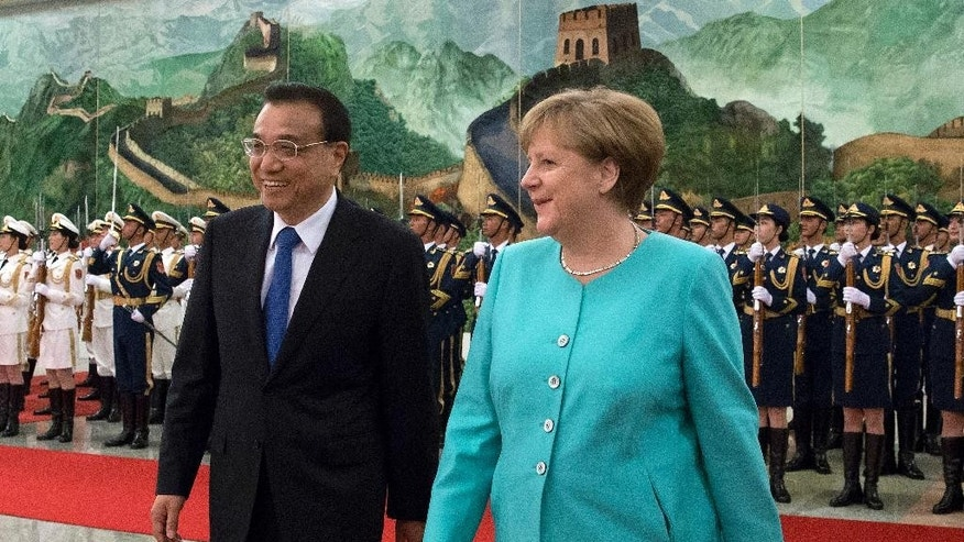 Germany's Chancellor Angela Merkel, right, chats with China's Premier Li Keqiang during a welcome ceremony at the Great Hall of the People in Beijing, Monday, June 13, 2016. (AP Photo/Andy Wong)