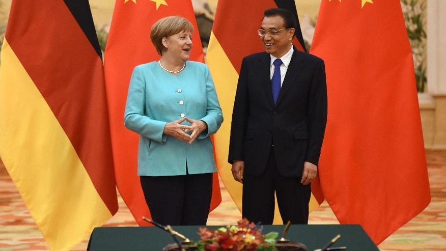 Germany'a Chancellor Angela Merkel, left,  chats China's Premier Li Keqiang duing a signing ceremony at the Great Hall of the People in Beijing, on Monday, June 13, 2016. Merkel is on a three day visit to China from June 12-14. (Wang Zhao, Pool Photo via AP)