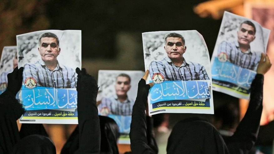 FILE- In this Thursday, May 14, 2015 file photo, Bahraini anti-government protesters hold up images of jailed human rights activist Nabeel Rajab during a solidarity protest outside his home in Bani Jamra, Bahrain. A prominent activist in Bahrain has been detained by authorities after a raid on his home. The family of Nabeel Rajab and an activist group, Human Rights First, say he was taken into custody early on Monday morning.(AP Photo/Hasan Jamali, File)
