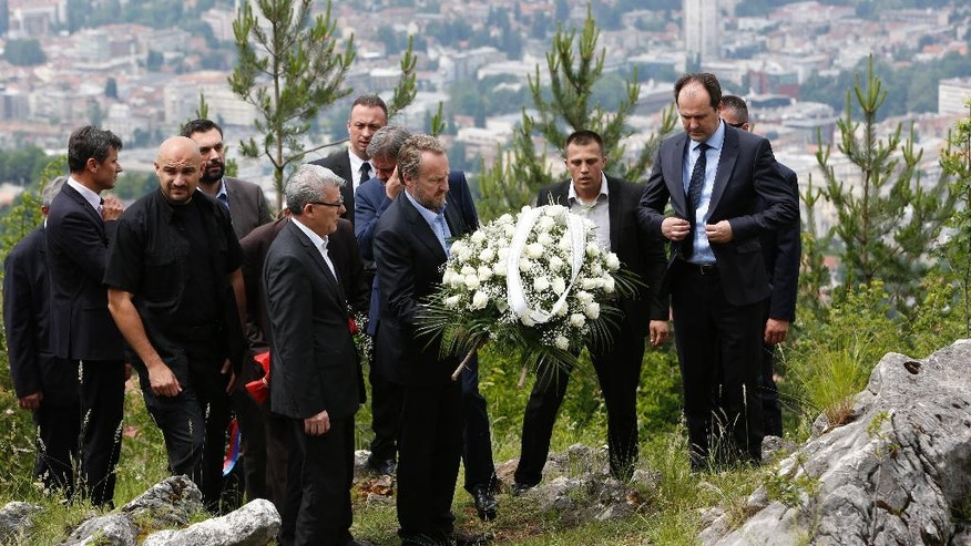 Bosnian Muslim leader Bakir Izetbegovic member of Bosnian Presidency, front centre, lays a wreath as he pays tribute to at least 30 Bosnian Serbs who were killed by paramilitary group during the 1992-95 Bosnian war in Sarajevo, Bosnia, Monday, June 13, 2016.   The first Bosnian Muslim leader to visit the site, Izetbegovic is visiting the mountain where at least 30 Bosnian-Serbs were thrown into an abyss by a paramilitary unit seeking revenge for a Serb nationalist siege on the capital. The city of Sarajevo behind. (AP Photo/Amel Emric)