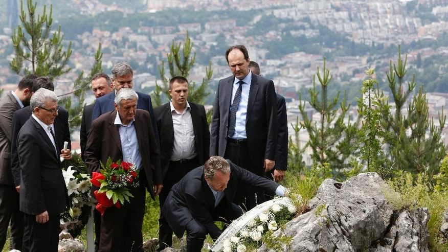 Bosnian Muslim leader Bakir Izetbegovic member of Bosnian Presidency, front right, lays a wreath as he pays tribute to at least 30 Bosnian Serbs who were killed by paramilitary group during the 1992-95 Bosnian war in Sarajevo, Bosnia, Monday, June 13, 2016.   The first Bosnian Muslim leader to visit the site, Izetbegovic is visiting the mountain where at least 30 Bosnian-Serbs were thrown into an abyss by a paramilitary unit seeking revenge for a Serb nationalist siege on the capital.  (AP Photo/Amel Emric)