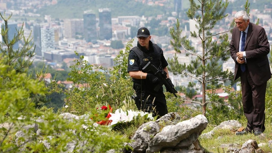 Member of police forces secure an area while Bosnian Serb Miladin Vidakovic member of the Serb Civil Council from Sarajevo looks on, near the spot where 30 Bosnian Serbs were killed by paramilitary group during the 1992-95 Bosnian war in Sarajevo, Bosnia, Monday, June 13, 2016.  The first Bosnian Muslim leader to visit the site, Izetbegovic is visiting the mountain where at least 30 Bosnian-Serbs were thrown into an abyss by a paramilitary unit seeking revenge for a Serb nationalist siege on the capital. The city of Sarajevo behind.(AP Photo/Amel Emric)