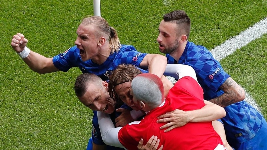 A Croatian fan enters the field to celebrate as Croatia's Luka Modric celebrates with Ivan Perisic and Domagoj Vida after scoring his side's first goal during the Euro 2016 Group D soccer match between Turkey and Croatia at the Parc des Princes stadium in Paris, France, Sunday, June 12, 2016. (AP Photo/Francois Mori)