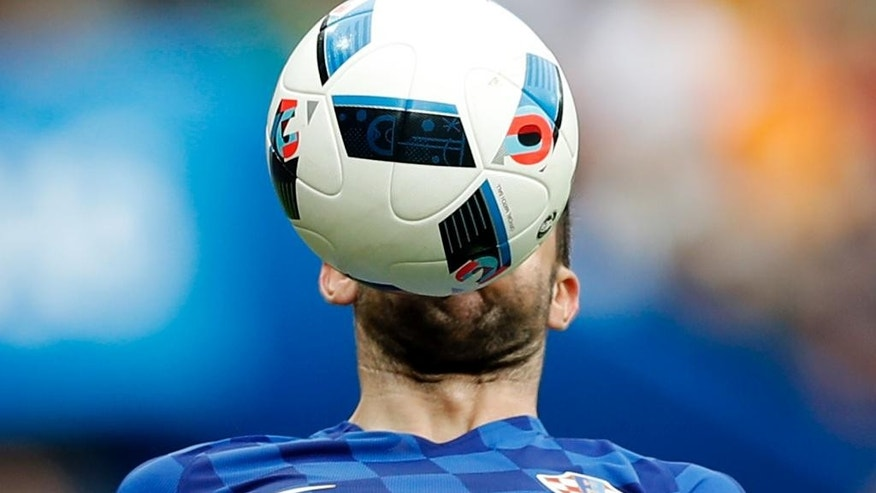 Croatia's Darijo Srna gets the ball on his face, during the Euro 2016 Group D soccer match between Turkey and Croatia at the Parc des Princes stadium in Paris, France, Sunday, June 12, 2016. (AP Photo/Christophe Ena)