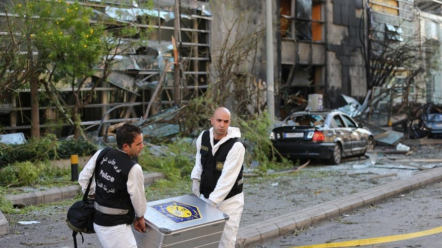 Police investigators carry equipment in front the damaged headquarters building of Blom Bank where a bomb exploded Sunday evening, in Beirut, Lebanon, Monday, June 13, 2016. Blom Bank has been criticized by some pro-Hezbollah politicians for taking a hard-line position after Lebanese banks began abiding by a U.S. law that sanctions doing business with the militant group. Authorities say dozens of bank accounts related to Hezbollah's organizations have been closed in recent weeks. (AP Photo/Hussein Malla)