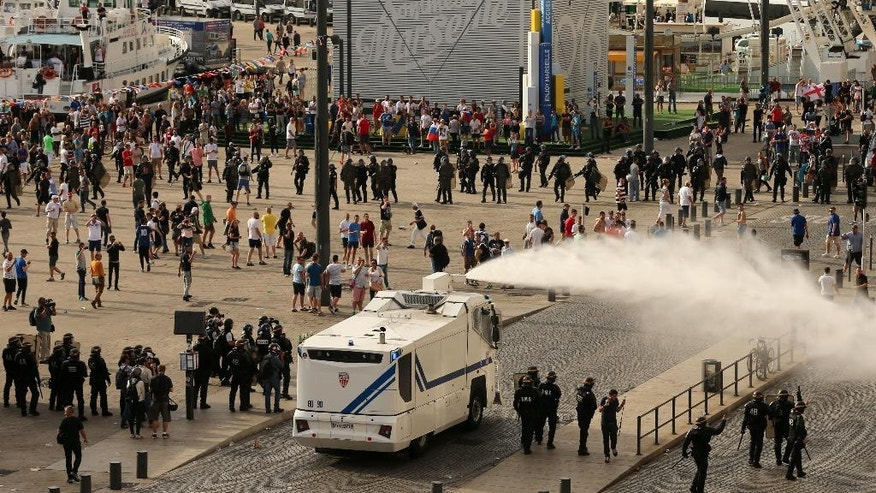 Police fire water cannons to control the fighting fter football fans clashed ahead of the England v Russia Euro 2016 soccer match, in Marseille, France, Saturday June 11, 2016.  Riot police have used tear gas canisters during clashes with soccer fans Saturday in Marseille's Old Port in a third straight day of violence during the Euro 2016 championships. (Niall Carson / PA via AP) UNITED KINGDOM OUT - NO SALES - NO ARCHIVES